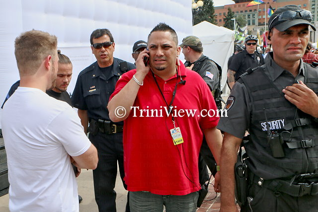 Event organizer Miguel Lopez (in red) among police officers in the process of shutting down the temporary enclosure